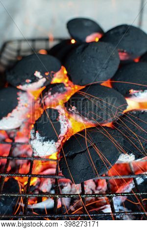 Pile Of Round Coal Briquettes On Grill Flaring Up Under Increased Air Flow, Ready For Bbq Very Soon,