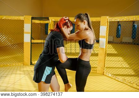 Female MMA fighter blocks knee hit, combat workout