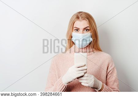 Frustrated Scared Woman In Gloves And Protective Mask With Smart Phone. Shocking Content, Bad News,