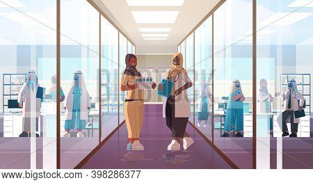 Black African Muslim Doctors In Uniform Discussing During Meeting In Hospital Corridor Medicine Heal