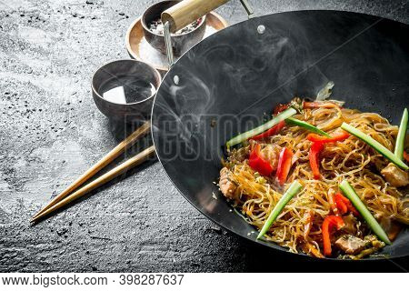 Chinese Wok. Hot Asian Cellophane Noodles In A Frying Pan Wok. On Dark Rustic Background