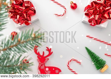 Noel Design. White Gift Box With Red Ribbon, New Year Balls And Winter Tree In Christmas Composition