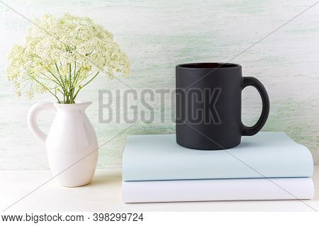 Black Coffee Mug Mockup With Tender White Flowers And Books. Empty Mug Mock Up For Brand Promotion.