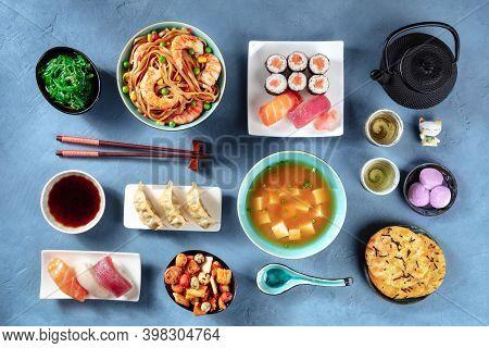Japanese Food, Sushi, Udon, Miso Soup, Tea, Mochi Etc, Overhead Flat Lay Shot On A Blue Background