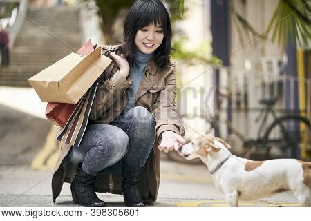 Young Asian Woman Returning From Shopping Trip Teasing A Dog On Street