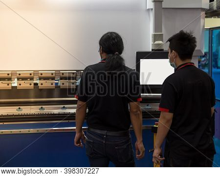 Industrial Technician Opearting Cnc Synchronize Hydraulic Press Brake. Metalworking Manufacturing Fa