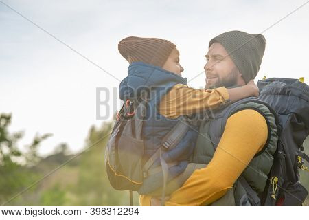 Young affectionate father with backpack holdng his cute little son on hands against natural environment against sky, green grass and bushes