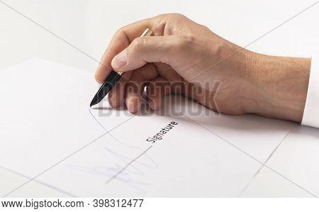 Closeup Of Businessman Hand Signing Contract, Signature Close Up.