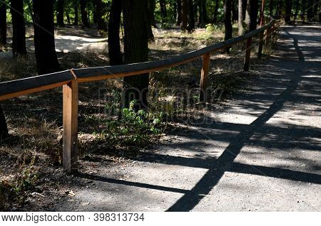 Forest Threshing Beige Gravel Roads In Sloping Terrain Have On One Side A Wooden Simple Fence Or Rai