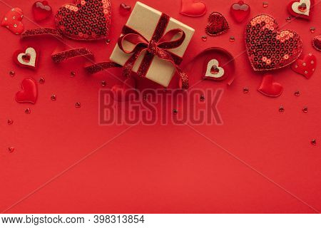 Festive composition with gift box and hearts on red background. Top view, copy space. Valentine's day concept.
