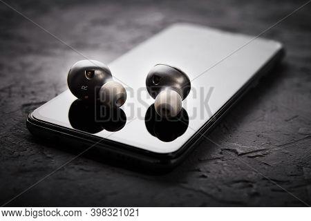 Wireless Earphones On A Smartphone. Bluetooth Headphones For Listen Audio