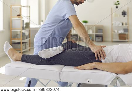 Confident Man Professional Doctor Osteopath Fixing Man Patinets Legs In Position To Fix Joints