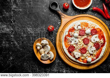 Preparation Pizza. Rolled Out Dough With Tomato Paste, Sausages, Mushrooms And Cheese. On Rustic Bac