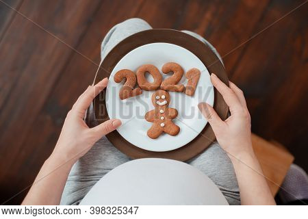 Close Up. Cropped Photo Of Pregnant Woman Holding Number 2021 Of Ginger Cookies Twins. People And Ex
