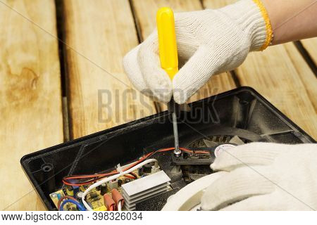 The Master Turns The Screw In The Electric Stove With A Screwdriver On A Wooden Background. Hands In