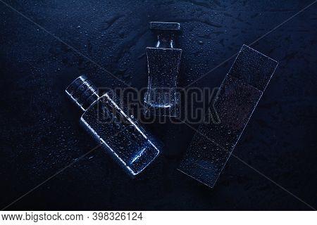 Three Different Perfumes On A Dark Background