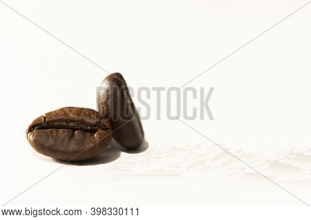 Grain Of Aromatic Black Coffee On A White Background. Background From Two Coffee Beans, Roasted Coff