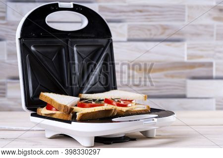 Making Cheese And Tomato Sandwiches On A Sandwich Press