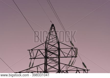 Power Line At Sunset. The Main Purpose Of Power Lines Is To Transmit Electric Current At A Distance.