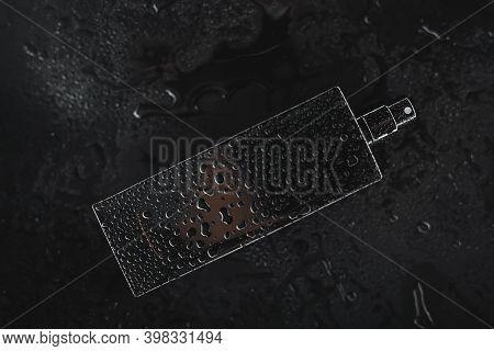Black Wet Perfume On A Dark Background