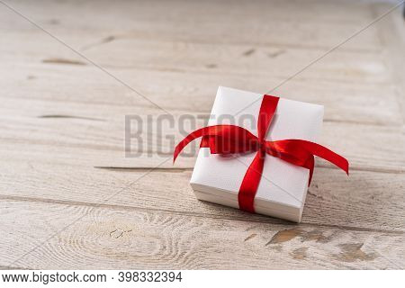 Gift Or Present Box With Red Bow On Wooden Background. Pastel Colors, Copy Space For Text And Design