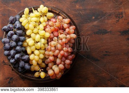 Various grapes on old wooden barrel. Top view flat lay with copy space