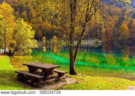 Alps, Northern Italy. Lake Fuzine. Cozy picnic corner - wooden table with benches. Yellow and orange trees are reflected in the green smooth water of the lake