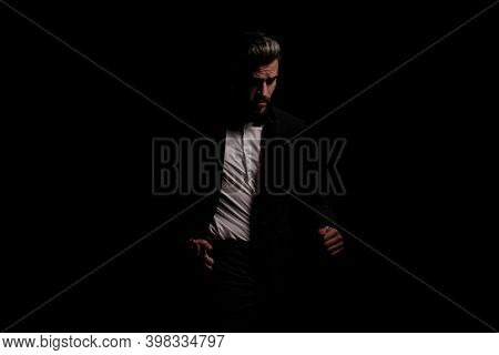 cool unshaved man in black velvet tuxedo holding hand in pocket, looking to side and walking on black background in studio