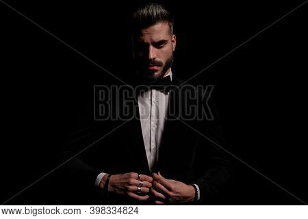 sexy confident bearded man buttoning black velvet tuxedo and posing in a fashion light on black background in studio