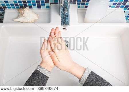 Child diligently soaping hands performing handwashing - basic protective measure against spreading of Coronavirus COVID-19 disease