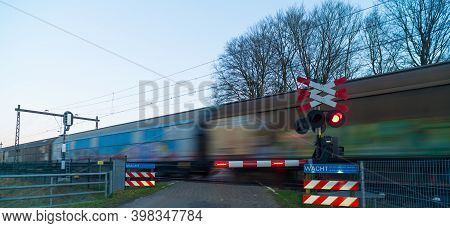 Cargo Train Passing By While Waiting For The Warning Lights