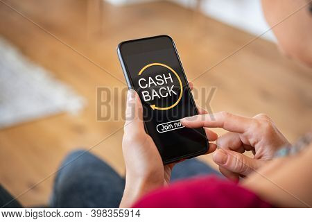 Woman taking benefit of cash back using smart phone, shopping and money refund concept. Close up hand holding smartphone with button to get started the cashback.