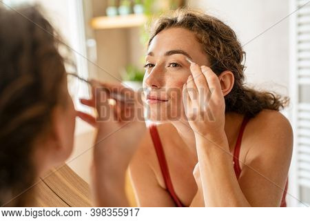 Beautiful young woman using tweezer on eyebrows. Pretty girl raising eyebrows using plucker before makeup. Beauty woman shaping eyebrows while looking in mirror.