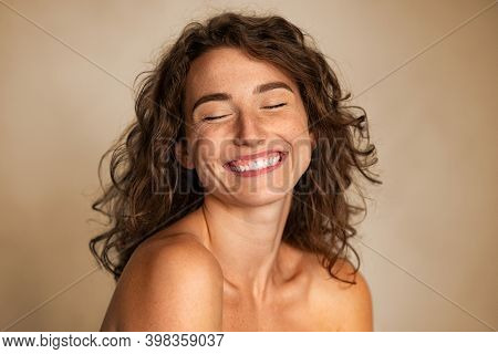 Close up of carefree young woman laughing. Portrait of smiling woman with freckles and closed eyes enjoying beauty treatment. Beautiful girl laughing isolated on background with copy space, skin care.