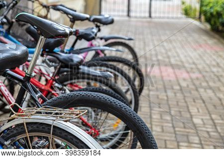 Bike Bicycle Parking In European City. Row Of City Parked Bicycles Bikes For Rent On A Sidewalk. Sof