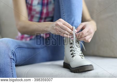 Woman Tying Shoelaces On White New Demi Leather Boots.