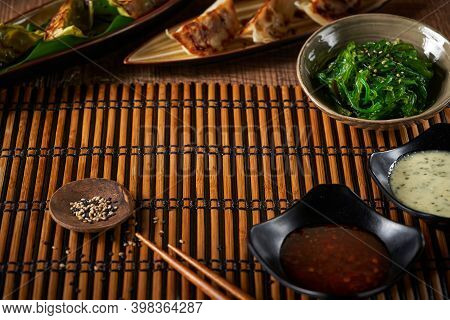 Sushi Set Backgound With Copy Space. Gyozas Dumplings And Wakame Salad, Sesame Seeds, Soy Sauce And
