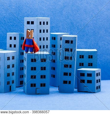 Super Clothespin Peg Hero, Red Blue Costume. Brave City Defender On The Top Of High-rise Building. A