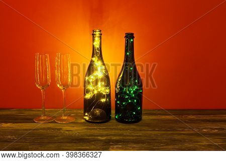 Festive Romantic Postcard Background. Shining Champagne Wineglasses, Wooden Table On Red. Cozy Still