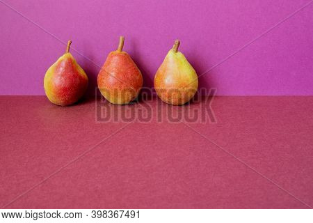 Still Life Composed Of Three Yellow Red Pears. Harvest Ripe Natural Organic Fruits On A Two-tone Pur