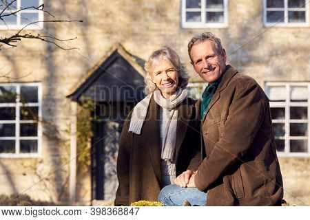Portrait Of Retired Senior Couple Standing Outside Home Together