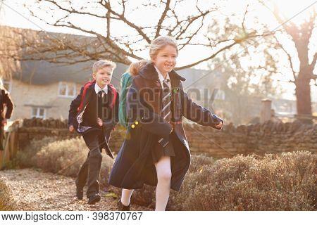 Children Wearing School Uniform  Returning Home From School Running Down Path