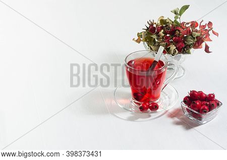 Organic Red Hawthorn Tea In Transparent Cup, Fresh Hawthorn Berries, Rose Hip In Sunlight With Shado