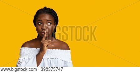 Secret Offer. Mysterious Black Woman Holding Finger Near Lips, Young African American Lady Making Sh