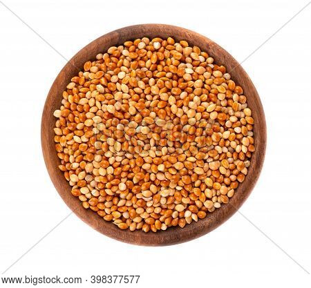 Millet In Wooden Bowl, Isolated On White Background. Unpeeled Millet Seeds. Top View.