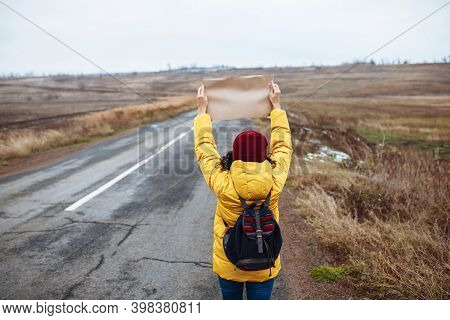 Backview Of A Woman Tourist Wearing Yellow Jacket And Red Hat Stands With A Poster Blank Paper On Th