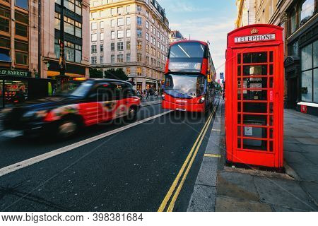 LONDON JULY 29,2019 : Icons of London. Black cab, red double decker bus and phone cabin at The Strand, a famous London Street