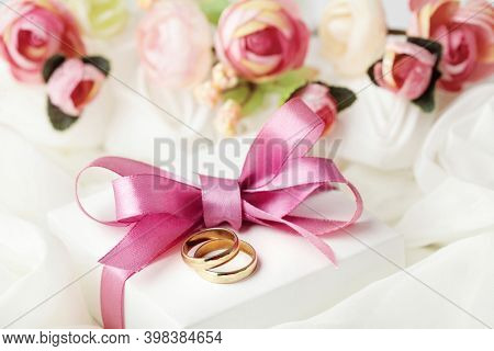 wedding background with wedding rings, gift box and flowers
