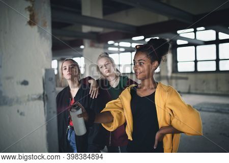 Group Of Teenagers Girl Gang Indoors In Abandoned Building, Using Spray Paint On Wall.