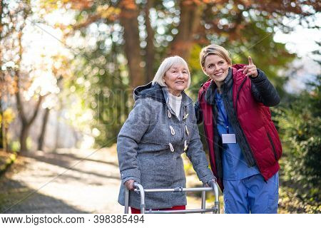 Senior Woman With Walking Frame And Caregiver Outdoors On A Walk In Park, Coronavirus Concept.